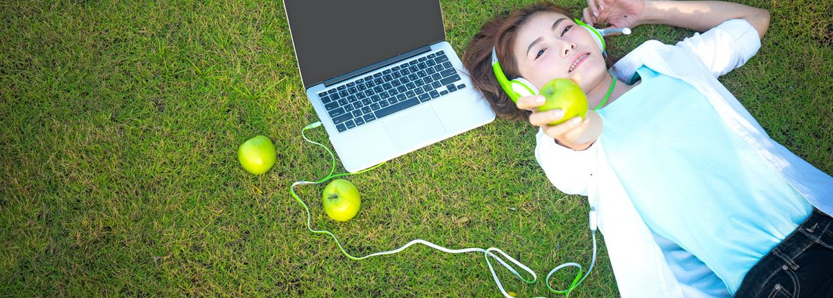 child laying on artificial grass with laptop