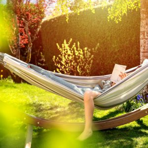 someone laying in hammock reading a book and relaxing