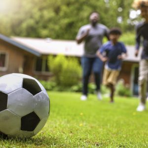 Family playing football on artificial grass
